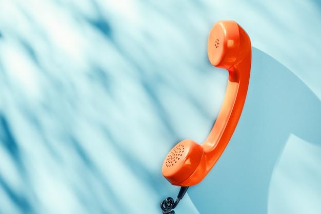 Оранжевая винтажная телефонная трубка на синей поверхности с красивыми естественными тенями
