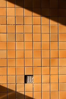Оранжевая стена имеет свет и тень.