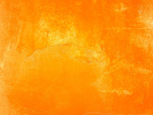Parete arancione con crepe e vernice scrostata.