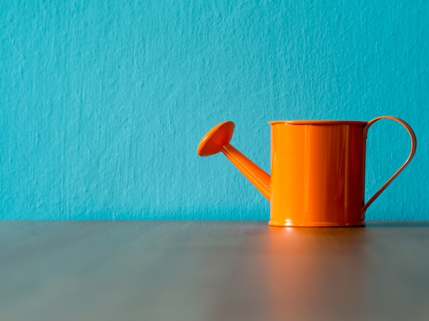 Orange watering cans put on wooden table