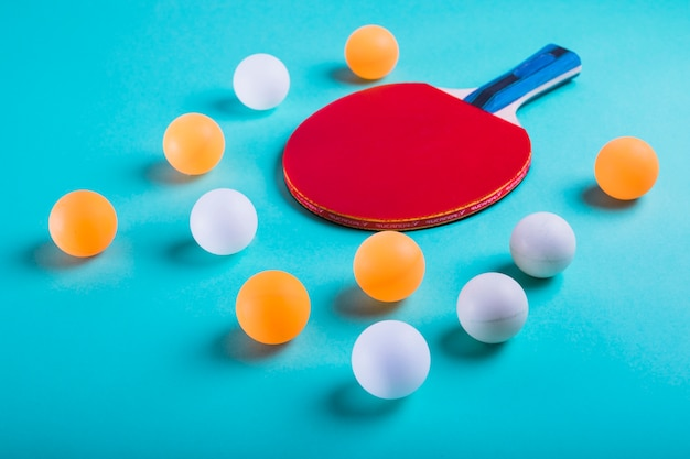 An orange and white balls with ping pong racket on blue background