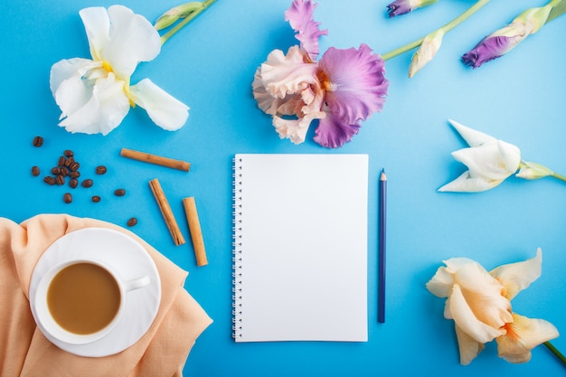 Orange, white, purple iris flowers with notebook and a cup of coffee on pastel blue