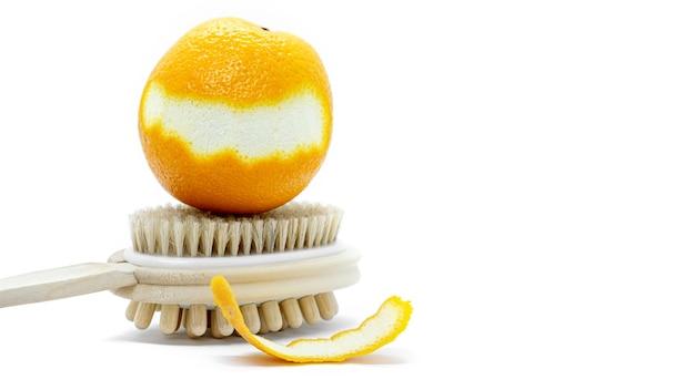 Апельсин с разрезанной кожурой на двухсторонней ручной массажной щетке для тела на белом фоне