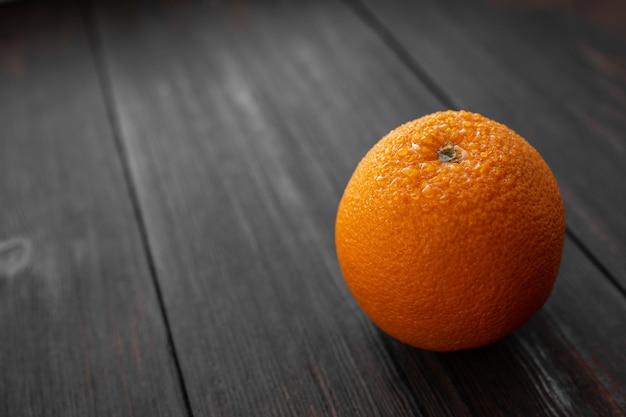 Апельсин с каплями воды на темном деревянном фоне