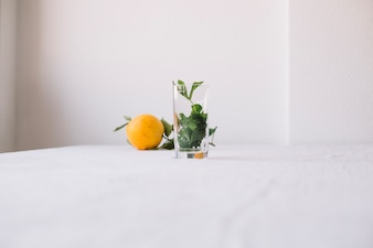 Orange with empty glass in composition