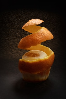Orange with peeled spiral skin on dark