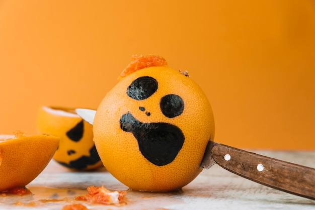 Orange with pictured face and knife inside