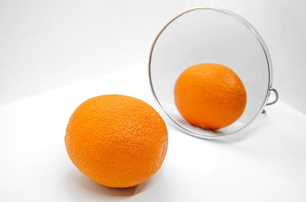 Апельсин с толстой кожурой в косметическом зеркале на белом
