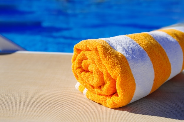 プールのサンラウンジャー背景に白いタオルとオレンジ