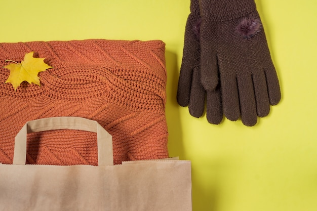 Orange woman warm sweater in paper craft package and brown gloves on yellow