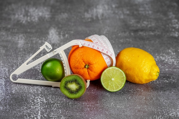 An orange wrapped with a measuring tape and a caliper surrounded by fresh fruits. the concept of slimming, remove cellulite, bring the figure into shape.