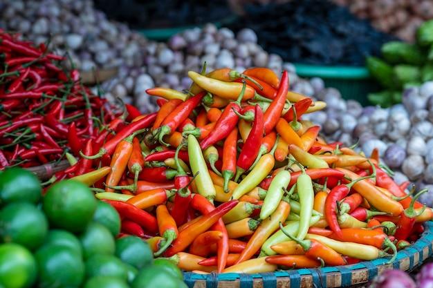 ベトナム、ハノイの旧市街の屋台の食べ物市場で販売されているオレンジ、黄色、赤のピーマン。閉じる
