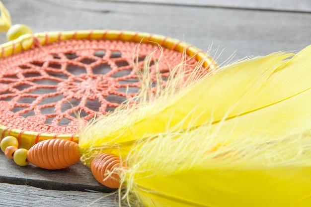 Orange yellow dream catcher on gray