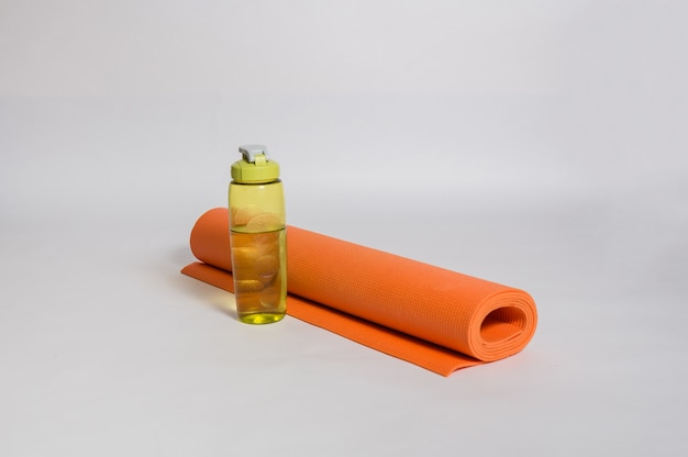 オレンジヨガマットとホワイトスペースに緑の水ボトル。孤立したスペースにある透明なウォーターボトルの横にある丸めたラグ。
