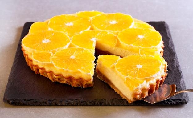 Orange and yogurt tart, sliced, on black board