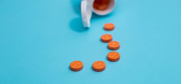 青いマットな背景にボトルから散らばっているオレンジ色の甘いビタミン錠剤