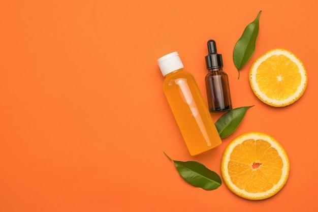 Апельсины, бутылка сока и медицинская бутылка на оранжевом фоне.