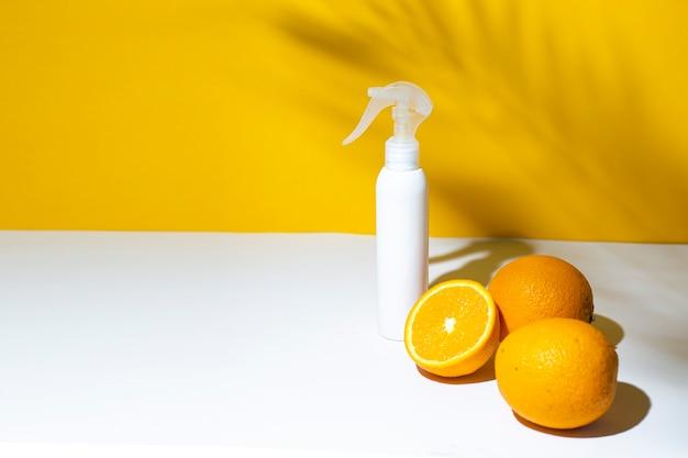 Апельсины и флакон с пульверизатором под тенью пальмы и солнечного света.