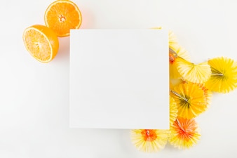 Oranges and cocktail umbrellas near paper sheet