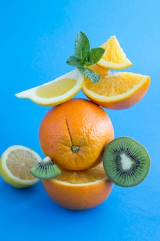 オレンジとキウイは青い背景にピラミッドを積み上げました。場所は垂直です。