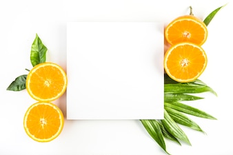 Oranges and leaves near paper sheet