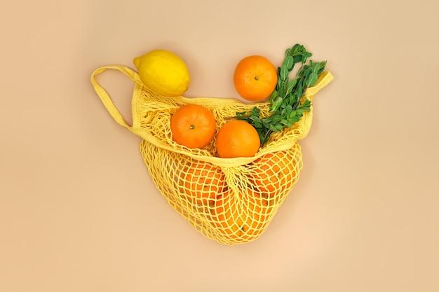 베이지 색 표면에 끈 가방에 민트 가지가있는 오렌지와 레몬