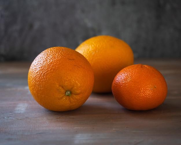 Апельсины и один мандарин лежат на грубо раскрашенном столе. крупным планом - три спелых плода.