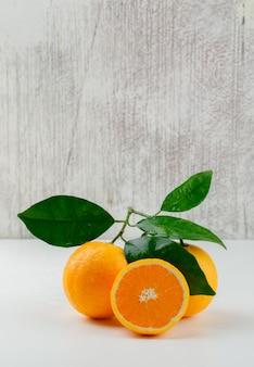 Апельсины и ломтик с веткой, вид сбоку.