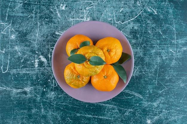 Апельсины и мандарин на тарелке, на мраморном столе.