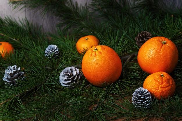 オレンジとコーン、クリスマス ホリデーの背景を持つモミの枝にみかん
