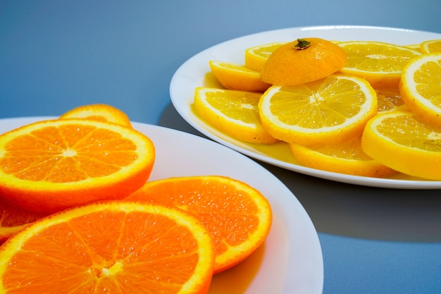 Апельсины и желтые лимоны на тарелке в солнечный день