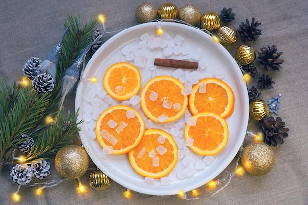 Апельсины на тарелке возле ветки елки, золотые шары и сосновые шишки. мандариновые украшения