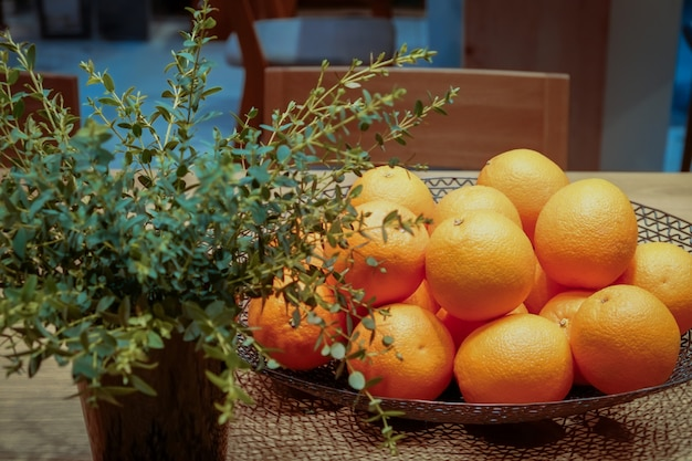 Oranges in a basket on the wooden table inside the dark room.