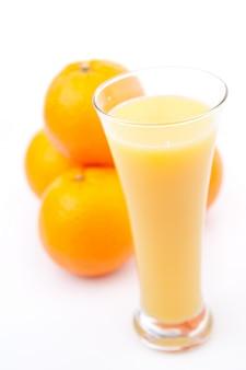 オレンジジュースのガラスの後ろにあるオレンジ