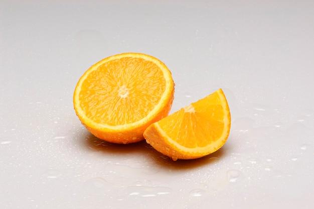 オレンジは、白い背景に分離された水滴で半分にカットされます。