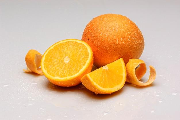 오렌지는 흰색 배경에 분리된 물방울로 반으로 자릅니다.