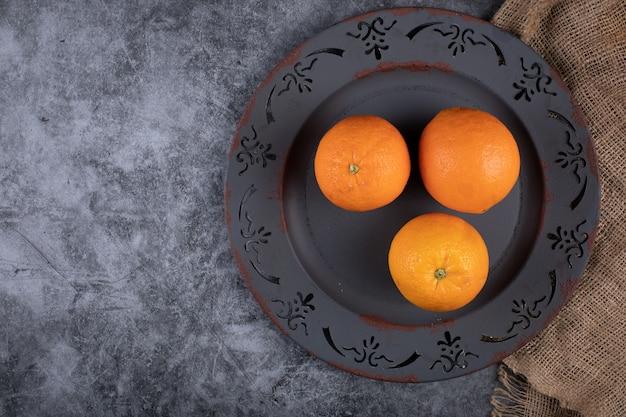 Oranges in a dark platter. top view.