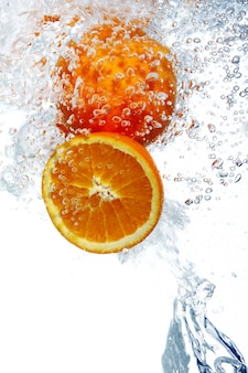 Oranges dropped into water