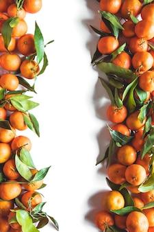 Композиция фруктов апельсинов с зелеными листьями и ломтиком на белом деревянном фоне, вид сверху