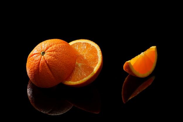 Плоды апельсина на черной поверхности