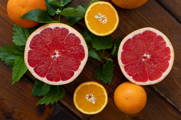 Oranges and grapefruit on a brown wooden background, top view, text space, citrus