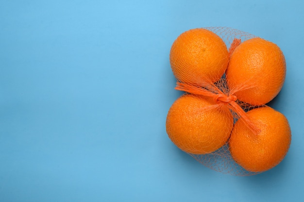 Oranges in a grid on a blue surface top view
