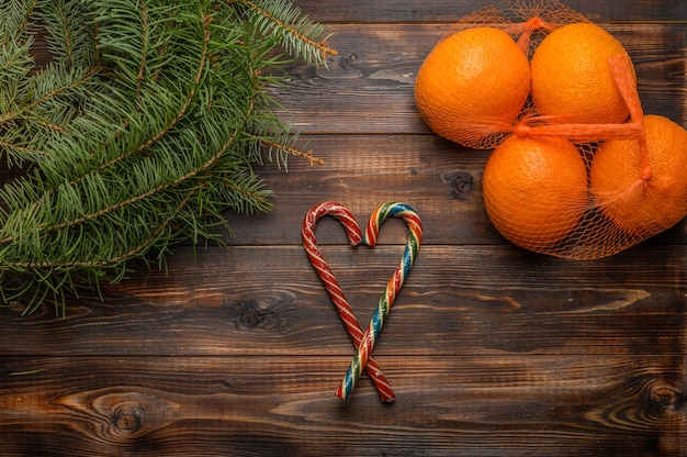 Oranges in a grid on a wooden surface near fir branches and caramel canes top view