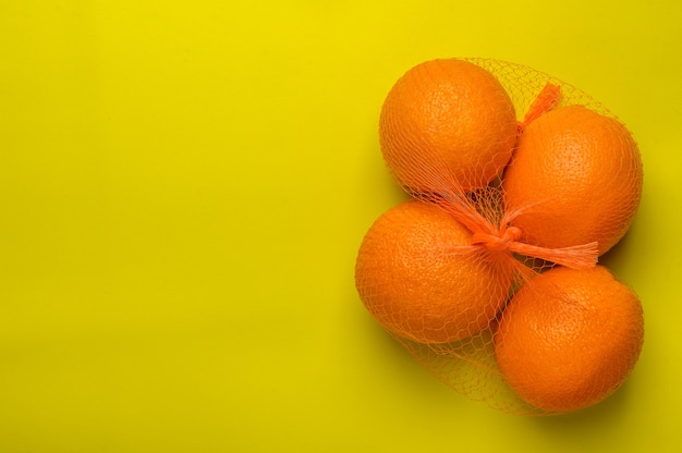 Oranges in a grid on a yellow surface top view