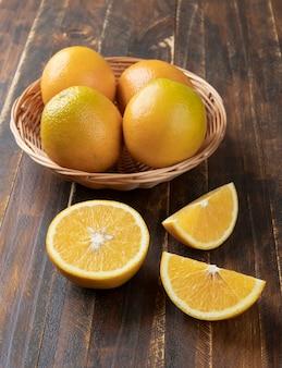 木製のテーブルの上にカットフルーツとバスケットのオレンジ。