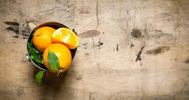 葉のバケツの中のオレンジ。木製の背景に。