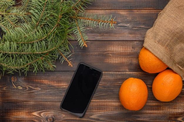 モミの枝と黒いスマートフォンのクリスマスの近くの木の表面にリネンバッグのオレンジ