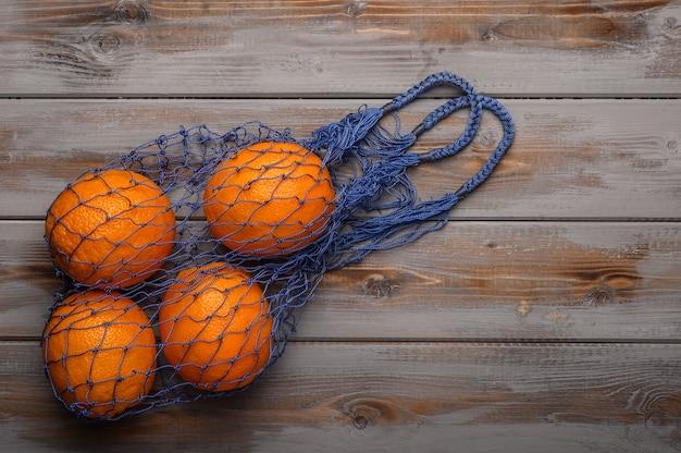 木の表面に天然素材で作られたメッシュストリングバッグのオレンジ