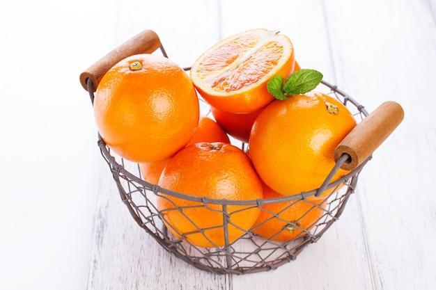 Апельсины в металлической корзине