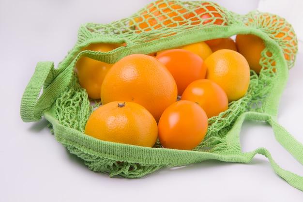 Апельсины в эко сумке на белом фоне